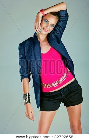 beautiful young woman with dramatic make-up and green pink manicure wearing shorts, dark navy blue linen jacket and pink neon watch on blue background