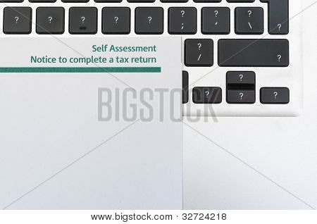 Detail of blank tax return form on top of computer keyboard with question marks in all keys and lots of copy space.