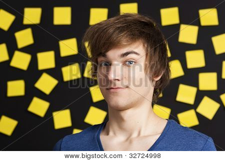 Young student in front of a board with yellow notes and looking in to the camera
