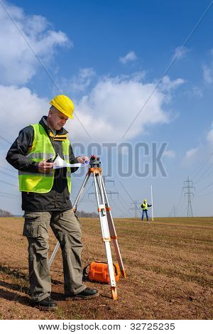 Land surveyors measuring with tacheometer  looking at plan construction site