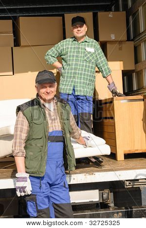 Two movers man loading furniture and boxes from truck vehicle