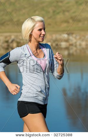 Young woman jogging recreational running by river sunny day