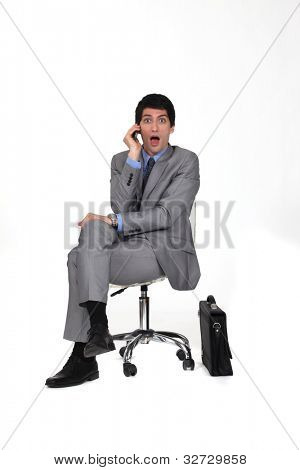 portrait of businessman sitting on swivel chair looking amazed