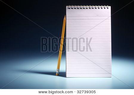 pencil resting on the plain nota pad