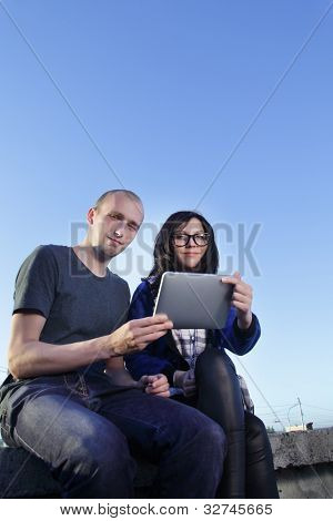 beauty girl and boy with tablet pc outdoors