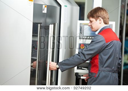 mechanical technician worker near modern cnc metal machining milling center in tool workshop