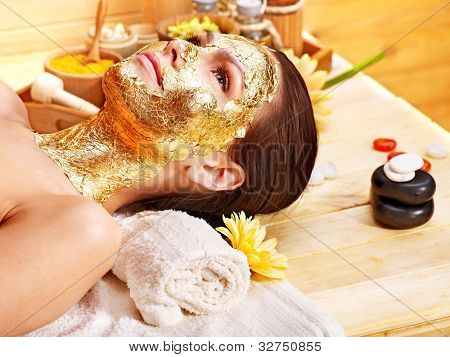 Woman getting  gold facial mask.