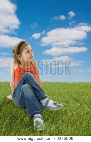 Cute Girl Sitting On The Green Grass