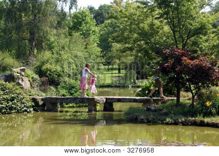 Woman And Child Walking Across A Bridge