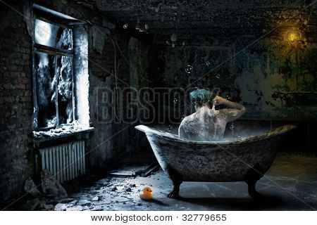 Alone sad man taking bath in abandoned room at night