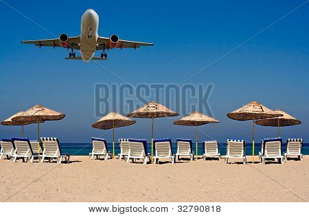 Jet Flying Over Sunloungers On An Empty Beach