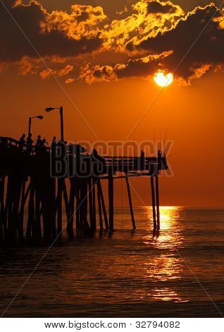 Silhouetted Fishermen At Sunrise On A Fishing Pier In North Carolina
