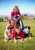 foto of human pyramid  - Cute Kids Building a Human Pyramid outdoors - JPG