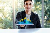 Customer Experiences Concept. Happy Young Man Sitting At The Desk And Presenting His Five Star Ratin poster