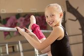 stock photo of leg warmer  - Little ballerina girl with leg on bar in dance studio - JPG