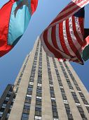 pic of rockefeller  - Verical shot of the Rockefeller Plaza office building with billowing flags covering the midpoint - JPG