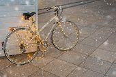 Christmas Bicycle. Vintage White Bike Decorated With Christmas Lights On Christmas Fair During Falli poster