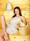 Young woman in sauna. Overheating danger.