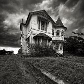foto of derelict  - A derelict old mansion stands alone on top of the hill as the storm slowly builds - JPG
