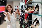 Woman Holding Black Heeled Shoe And Red Defocused Heeled Shoe In Shop. Photo With Depth Of Field poster