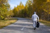 Hiker Or Traveler With A Backpack Goes On The Road In The Autumn Forest. Hiking. Hitch-hiking. Male  poster