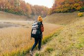 A Woman With A Heavy Backpack Is Walking Along The Path To The Forest. Autumn Concept. Healthy Lifes poster