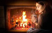 Beauty young Christmas woman sitting near fireplace in dark room at home and drinking hot beverage f poster