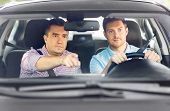 driver courses and people concept - car driving school instructor teaching young man to drive poster