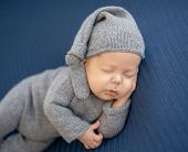Sweet newborn in knitted suit resting on side with hand under head poster