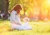 Happy pregnant mother and daughter in the autumn park. Beauty nature scene with family outdoor lifes poster
