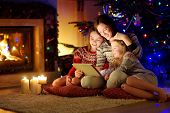 Mother And Her Two Cute Young Daughters Using A Tablet Pc At Home By A Fireplace In Warm And Cozy Li poster