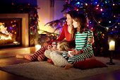 Happy Young Mother And Her Daughters Having A Good Time Sitting Together By A Fireplace In A Cozy Da poster