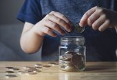 Cropped Shot Kid Hand Putting Money Coins Into Clear Jar,  Child Counting His Saved Coins, Childhood poster