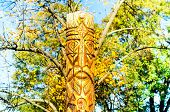 Wooden Idol Or Pagan God Against The Backdrop Of An Autumn Landscape. Close-up, Copy Space poster