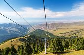 Summer Mountain Landscape High In The Mountains. Tall Trees Of Christmas Trees, Ski Lift At The Ski  poster