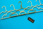 Many Empty Hangers Racks In Line Row With Tag On Bright Blue Color Table Background, Retail Male Fem poster