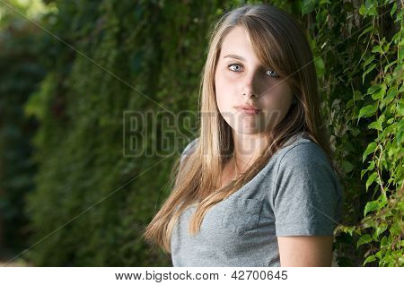 Teenage girl stands near vines in the shade