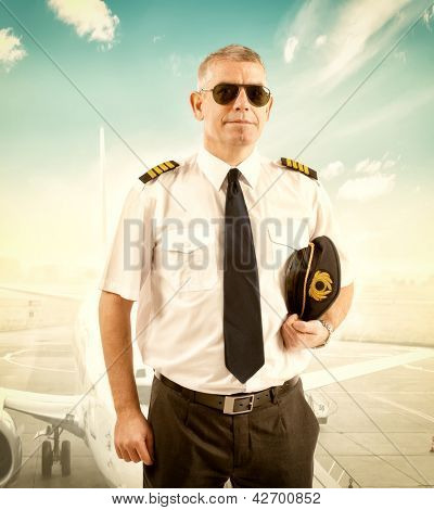 Cheerful pilot wearing uniform with epaulettes, standing with airliner in background.