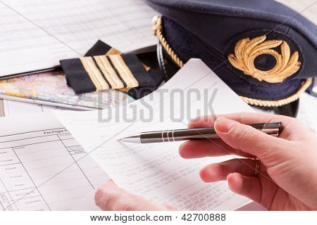 Close up of an airplane pilot hand filling in an flight plan and reading METAR with equipment including hat, epaulettes and other documents in background