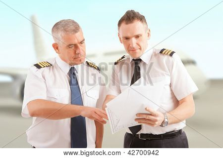 Airline pilots wearing uniform with epaulettes checking papers, passenger aircraft in background
