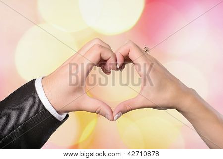 Hands bride and groom in a heart shape on a colored background defocused