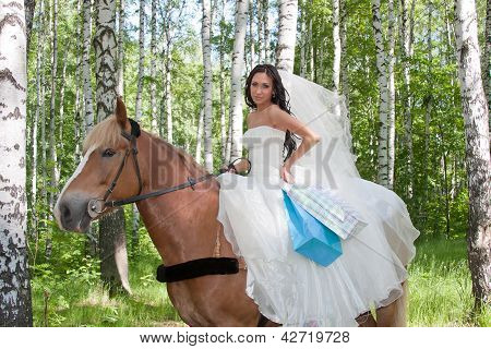 Young Woman In The Dress Of Fiancee On A Horse By A Canicular Day In A Birchwood