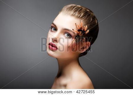 Portrait Of Woman With Brachypelma Smithi Spider Creeping On Her Face
