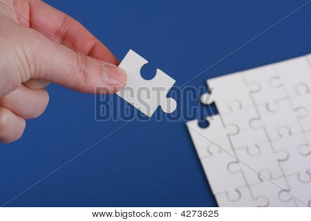Hand Holding Corner Of Jigsaw