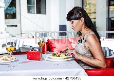 Smiling female having dinner at the restaurant