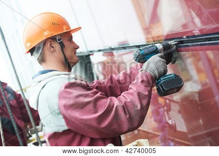 builders worker installing glass windows on facade of business building