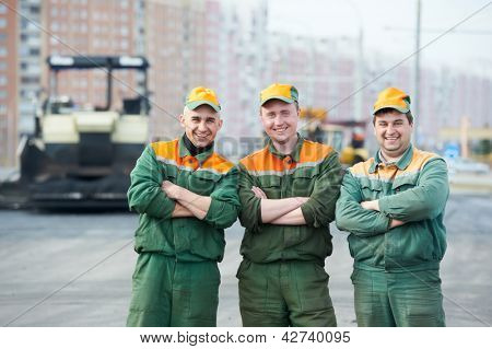 three happy road construction workers near asphalt paver machine