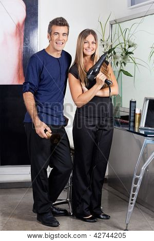 Full length portrait of male and female hairdressers standing together in salon
