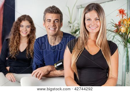 Portrait of happy hairdressers standing together in beauty parlor
