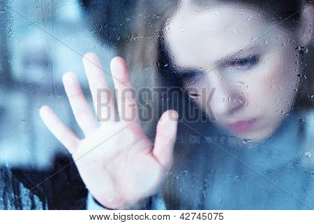 melancholische und traurige Mädchen am Fenster im Regen
